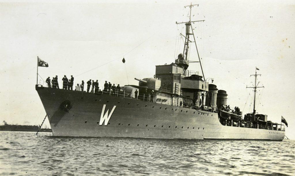 okręt wojskowy w porcie z widocznymi marynarzami na pokładzie