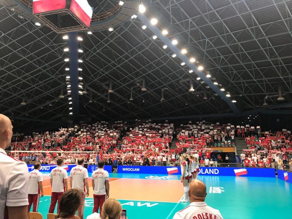 arena z boiskiem go gry w siatkówkę, w tle kibice podnoszą kartoniade tak, że powstała flaga Polski