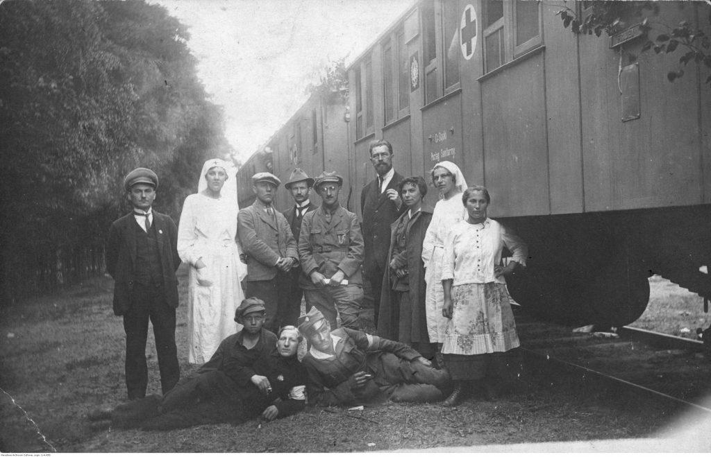 grupa mężczyzn i sanitariuszek pozuje przed pociągiem sanitarnym
