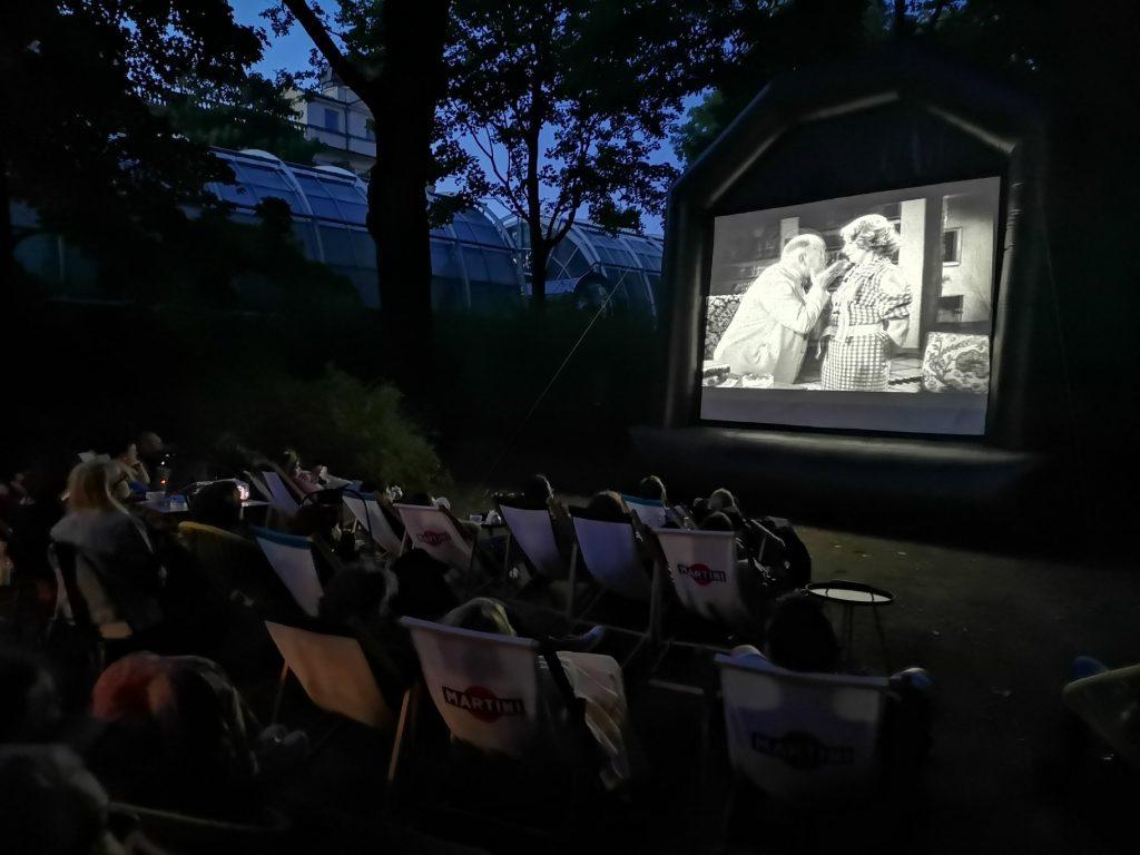 w ciemności na ekranie w plenerze wyświetlany filn, przed ekranem rzędy publiczności