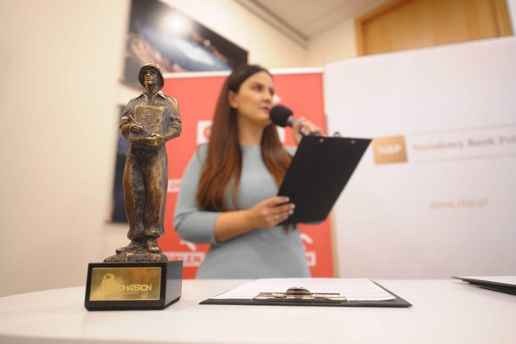 fotografia przedstawiająca statuetkę nagrody BohaterON, w tle sylwetka prowadzącej konferencję prasową