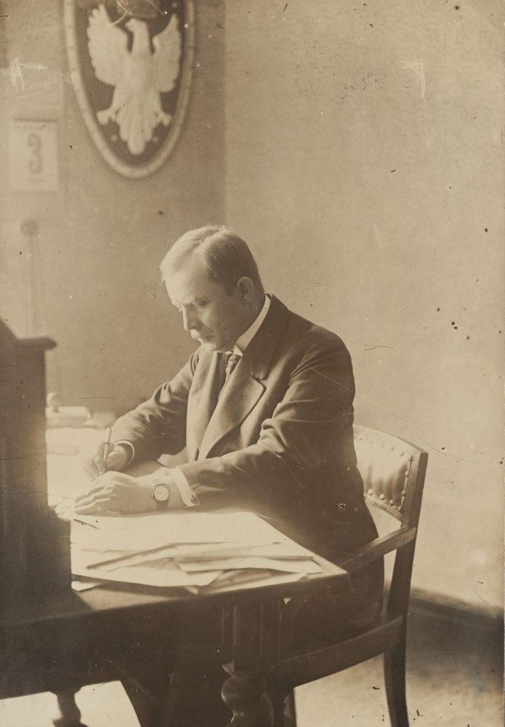Mężczyzna siedzący przy zarzuconym papierami biurku, w tle na ścianie godło z orłem i kalendarz
