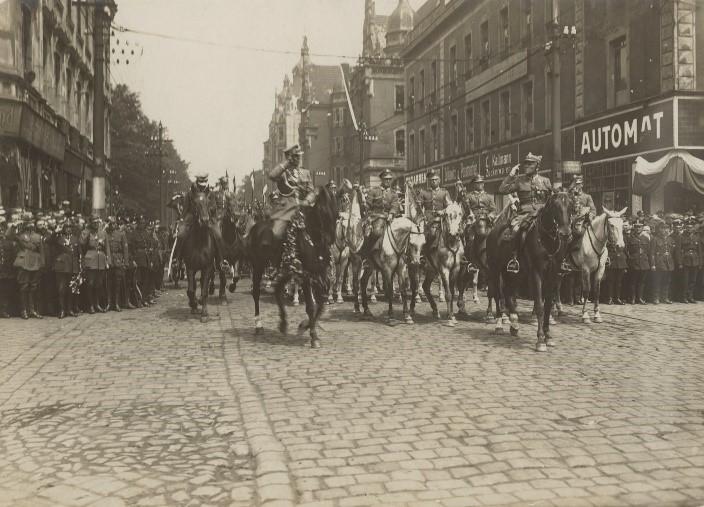 oddział konny jadący po ulicach miasta na archiwalnym zdjęciu