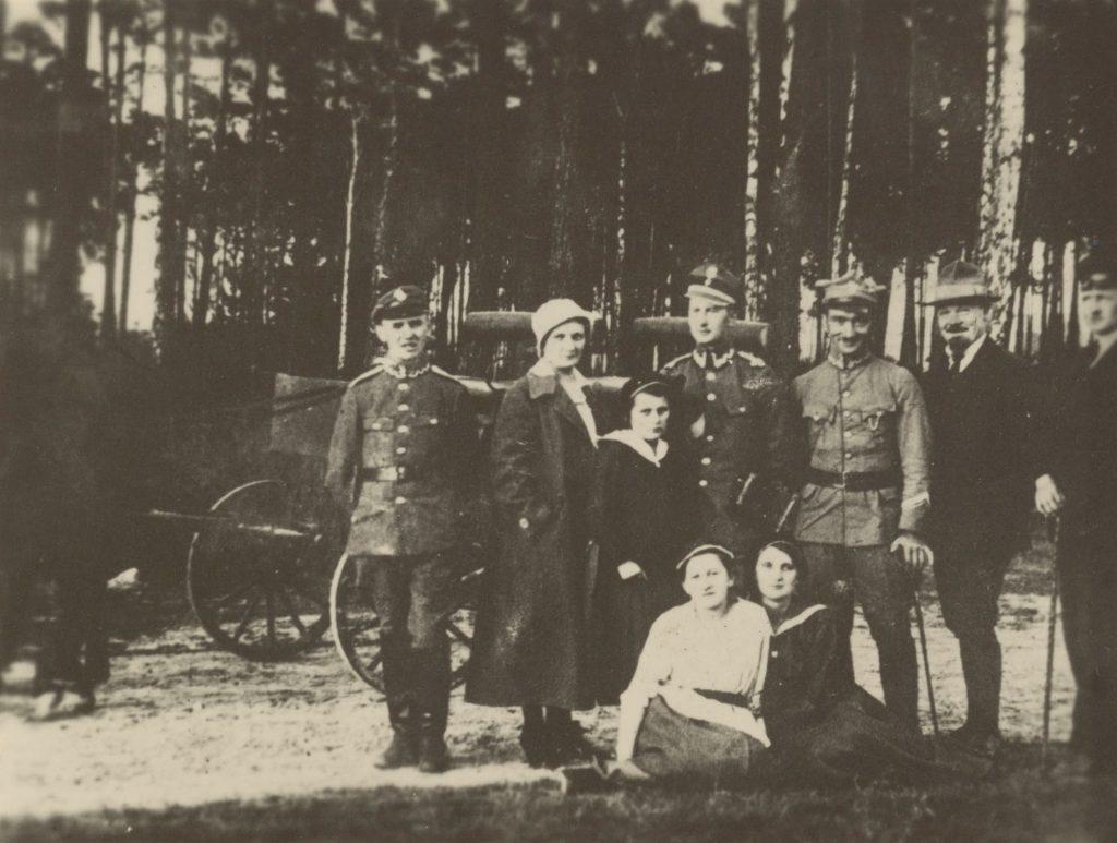 grupa kobiet i mężczyzn pozujących do fotografii w lesie, za nimi samochód