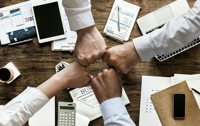 fotografia przedstawiająca cztery stykające się pięści w geście pracy drużynowej, nad biurkiem, na którym leżą akcesoria biurowe, tablet, kalkulator itp.