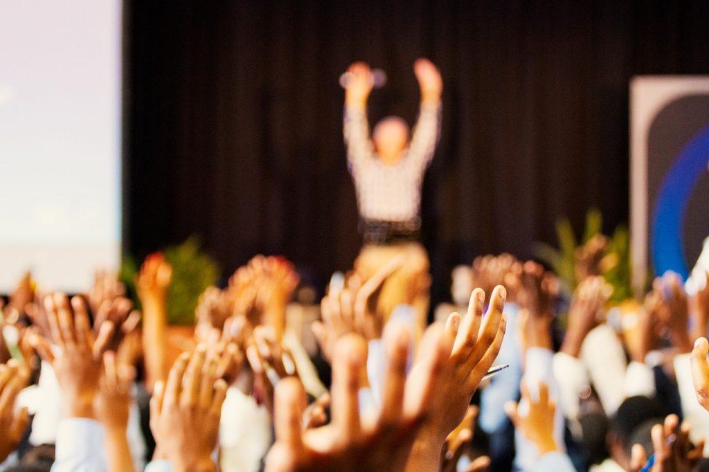 fotografia kolorowa, las rąk wzniesionych w geście zgłoszenia się do odpowiedzi, w tle prowadzący na scenie z mikrofonem