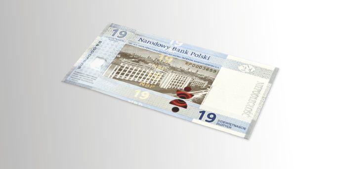 fotografia kolekcjonerskiego banknotu dziewiętnastozłotowego - rewers przedstawiający gmach Polskiej Wytwórni Papierów Wartościowych na tle panoramy współczesnej Warszawy