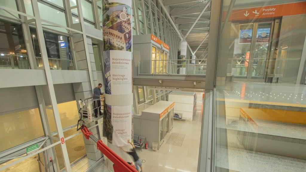 zdjęcie przedstawia mężczyznę montującego wystawę na filarach w hali portu lotniczego na Okęciu