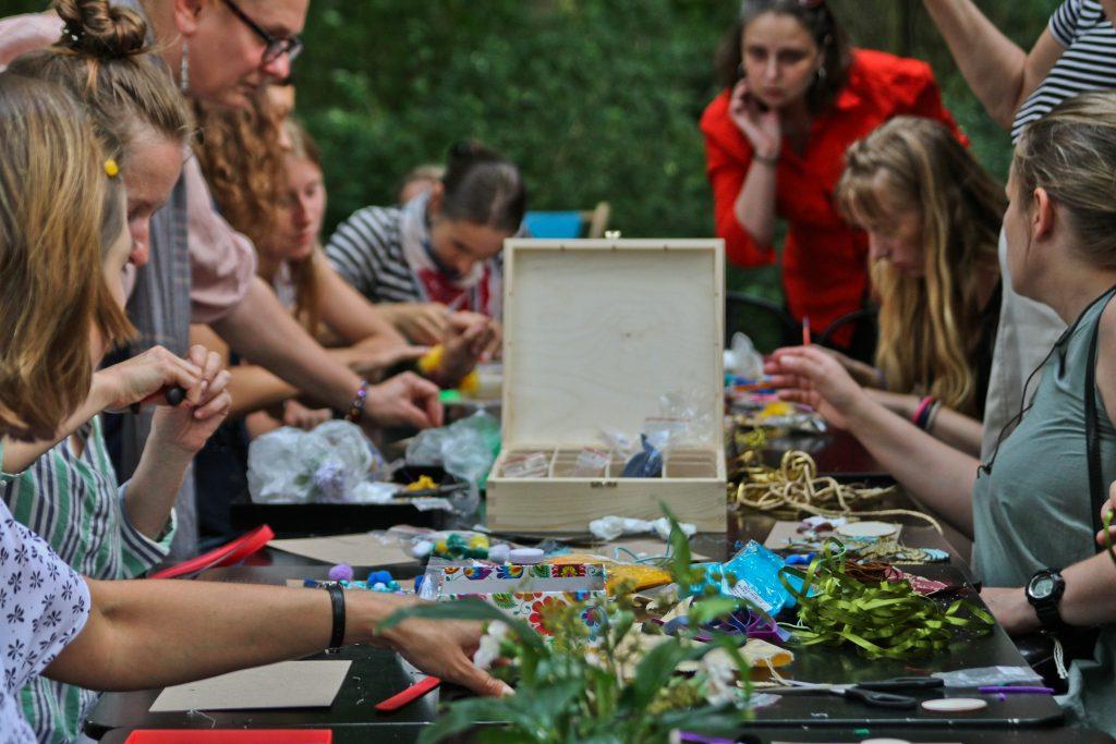 fotografia przedstawiająca grupę ludzi siedzącą przy stole pełnym materiałów rękodzielniczych