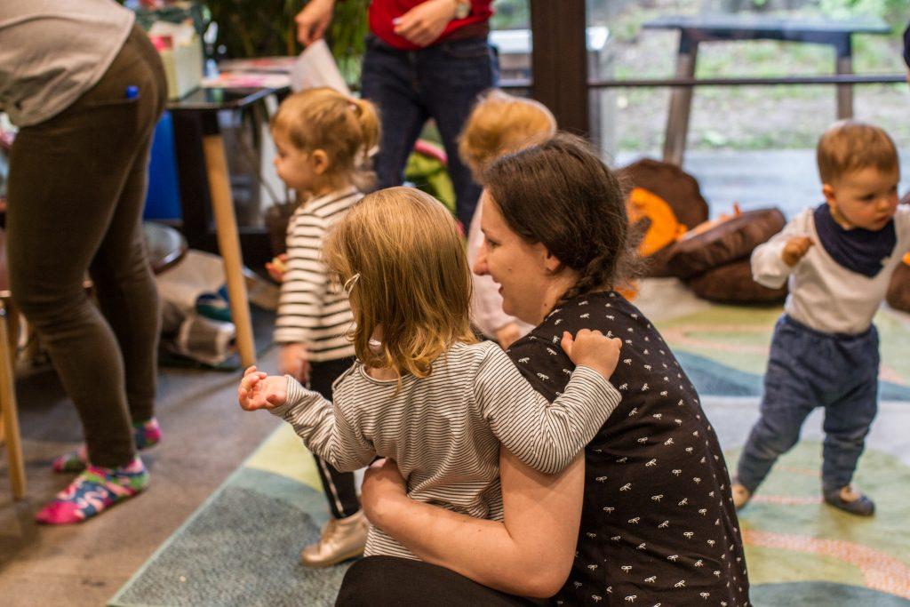 zdjęcie przedstawia kobietę przytulającą dziecko i dzieci biegające wokoło - ilustracja obrazująca warsztaty sensoryczne dla dzieci