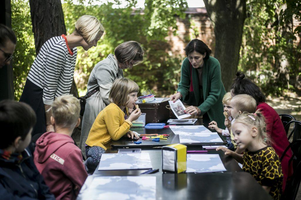 dzieci siedzące wokół stołu, wokół dorosłe kobiety prowadzące warsztaty