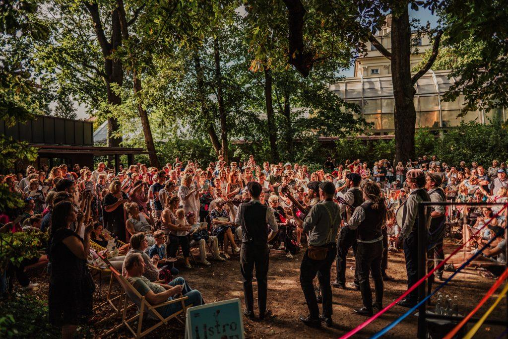 grupa ludzi zgromadzona w parku, obserwująca i śpiewająca wraz z zespołem muzyków