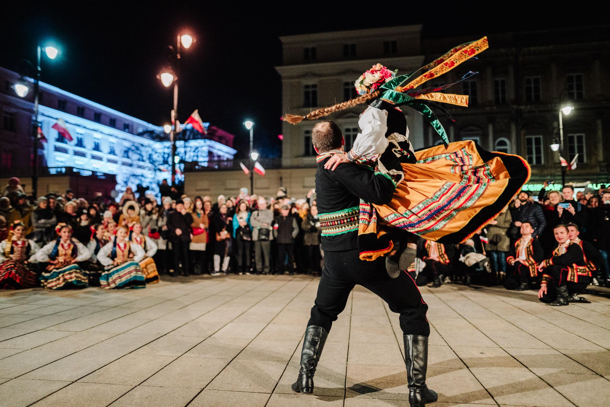 Na pierwszym planie. tańcząca para w strojach ludowych, w tle widzowie
