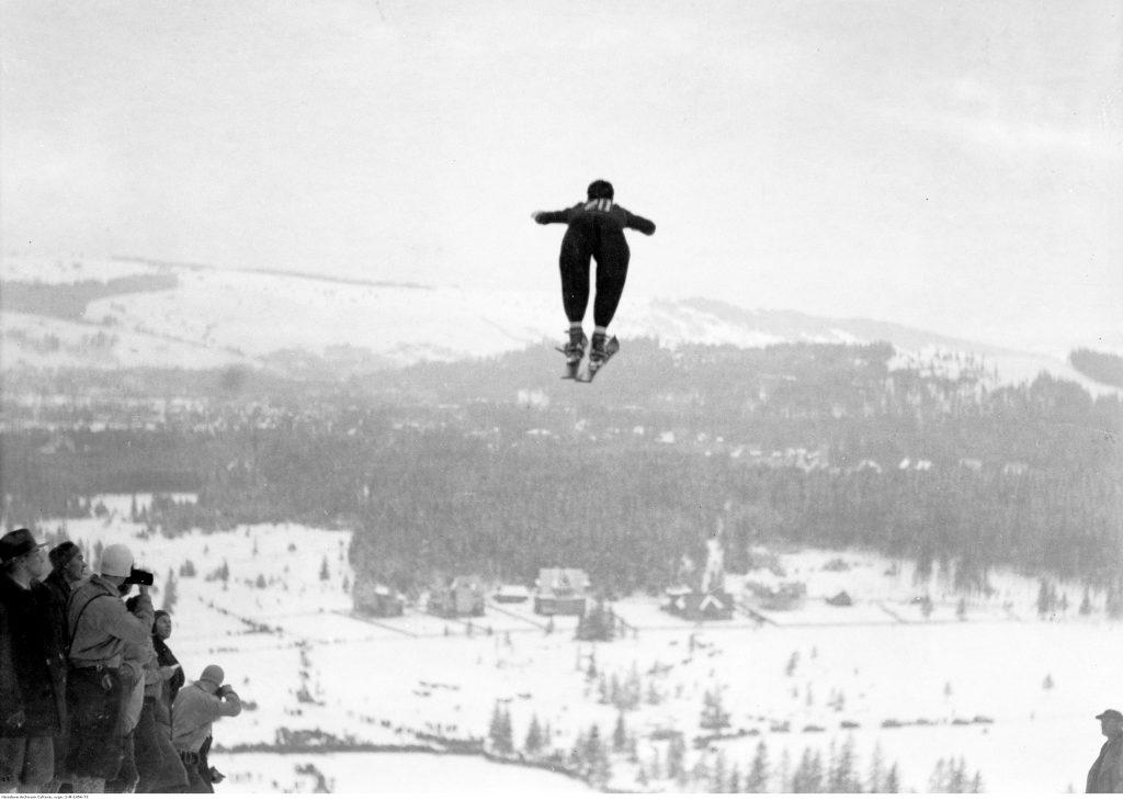 skoczek narciarski w locie, w tle widok na zabudowania miejskie