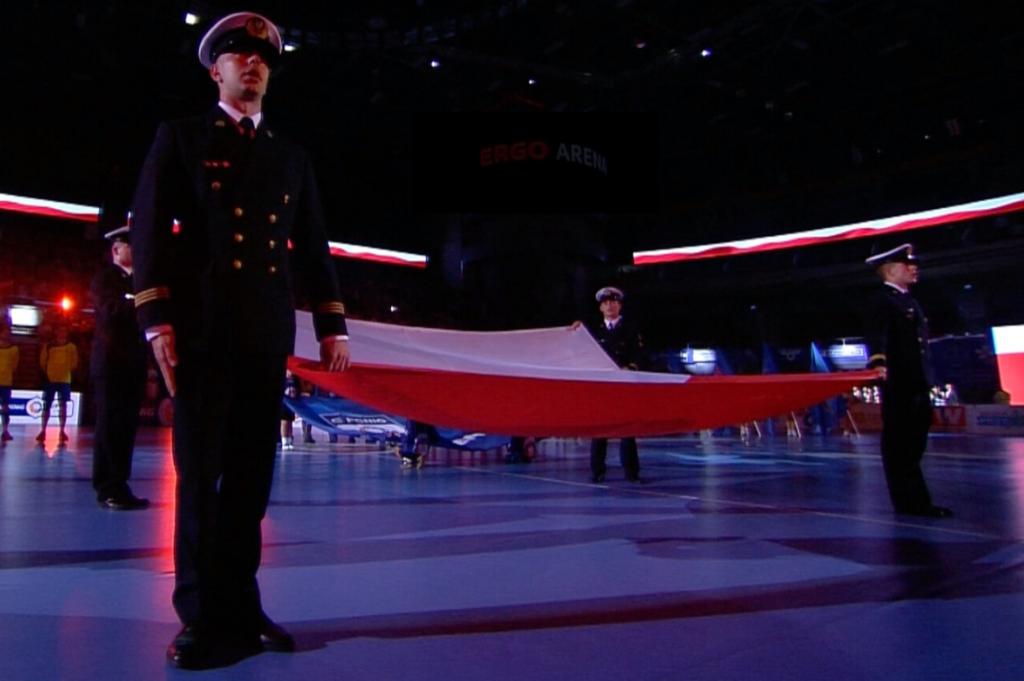 flaga polski trzymana przez 4 żołnierzy marynarki wojennej, w tle na baczność piłkarze ręczni