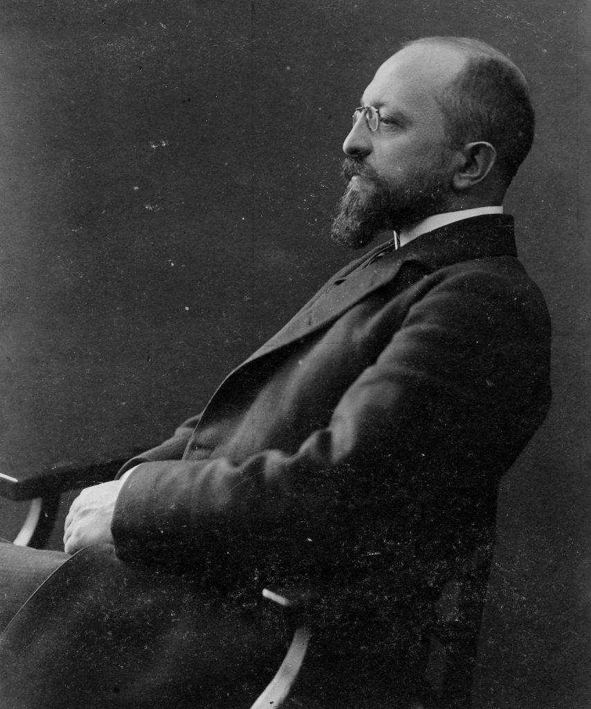 czarno-białe zdjęcie przedstawiające siedzącego na krześle mężczyznę