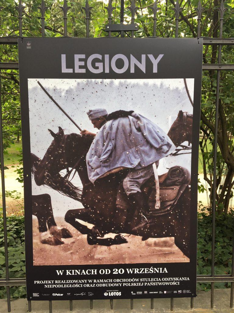 plansza ze zdjęciem kawalerzysty na koniu w trakcie walki zawieszona na płocie Łazienek