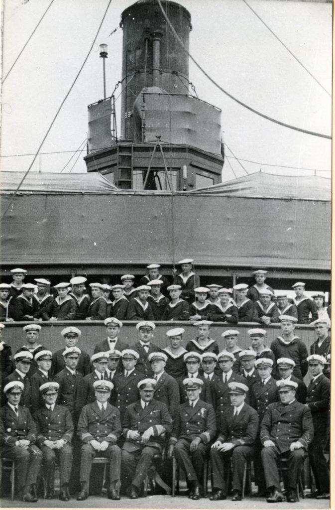 marynarze i kadra oficerska pozująca do zdjęcia przy okręcie