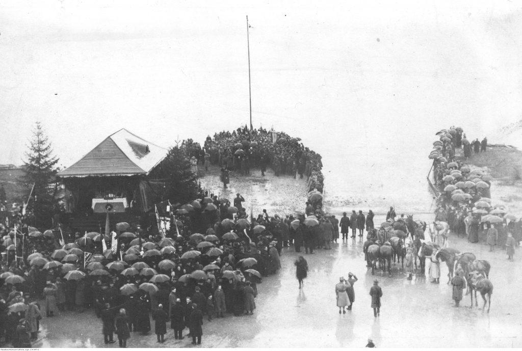 czarno białe zdjęcie z zaślubin, tłum z parasolkami stoi na wybrzeżu i patrzy w stronę morza