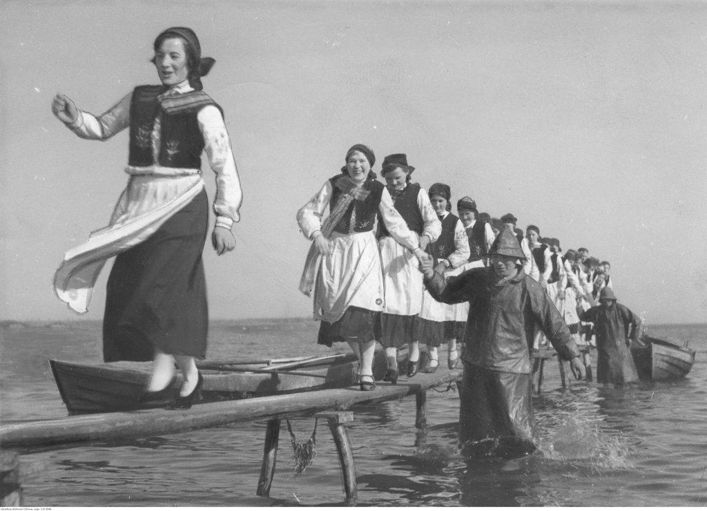 dziewczyny w strojach regionalnych idące po belce nad falami morza, którym pomagają stojący w wodzie rybacy w specjalnych strojach