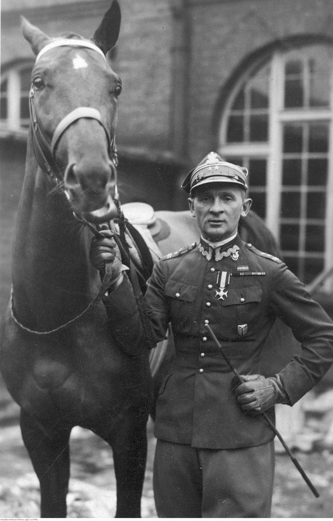 Karol Rómmel, podpułkownik kawalerii WP w mundurze, jeździec - fotografia sytuacyjna (stoi obok konia).