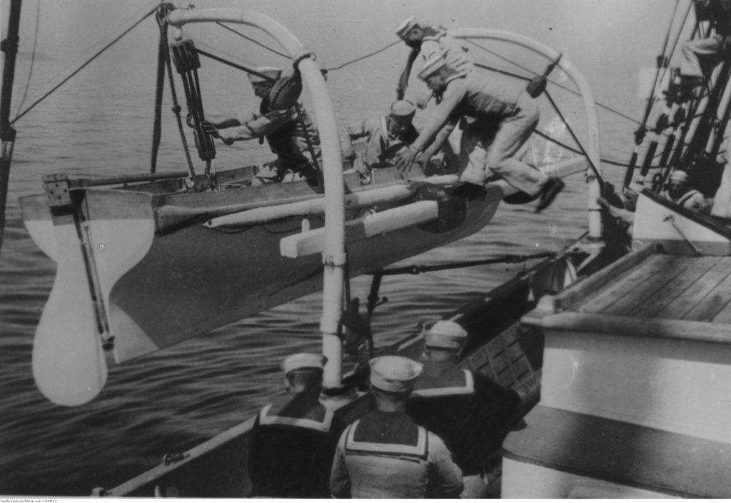 """Alarm """"Człowiek za burtą"""" na pokładzie szkunera ORP """"Iskra"""". Marynarze wskakują do szalupy ratunkowej."""