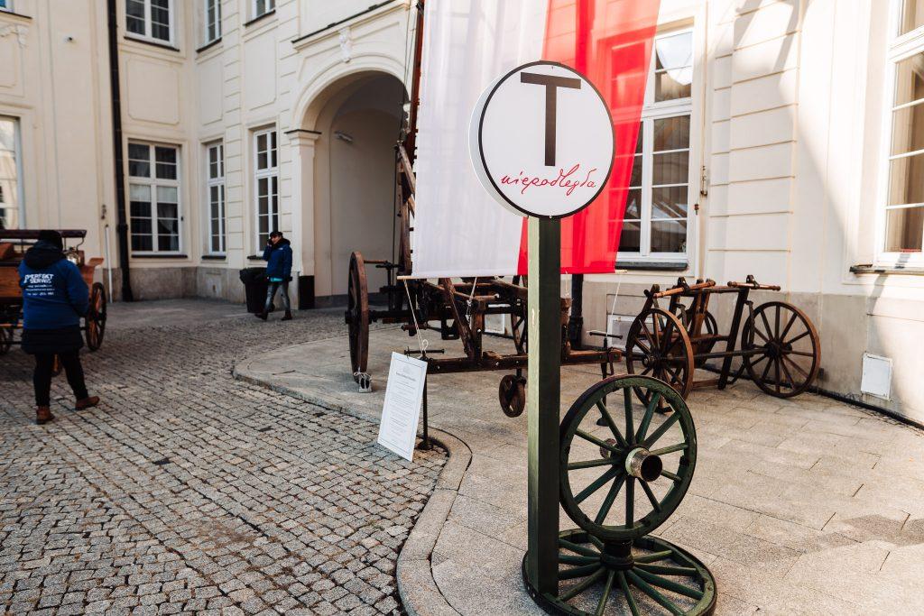 znak przystanku tramwajowego z logo Niepodległa, z tyłu zabytkowe sikawki i flaga na dziedzińcu MKiDN