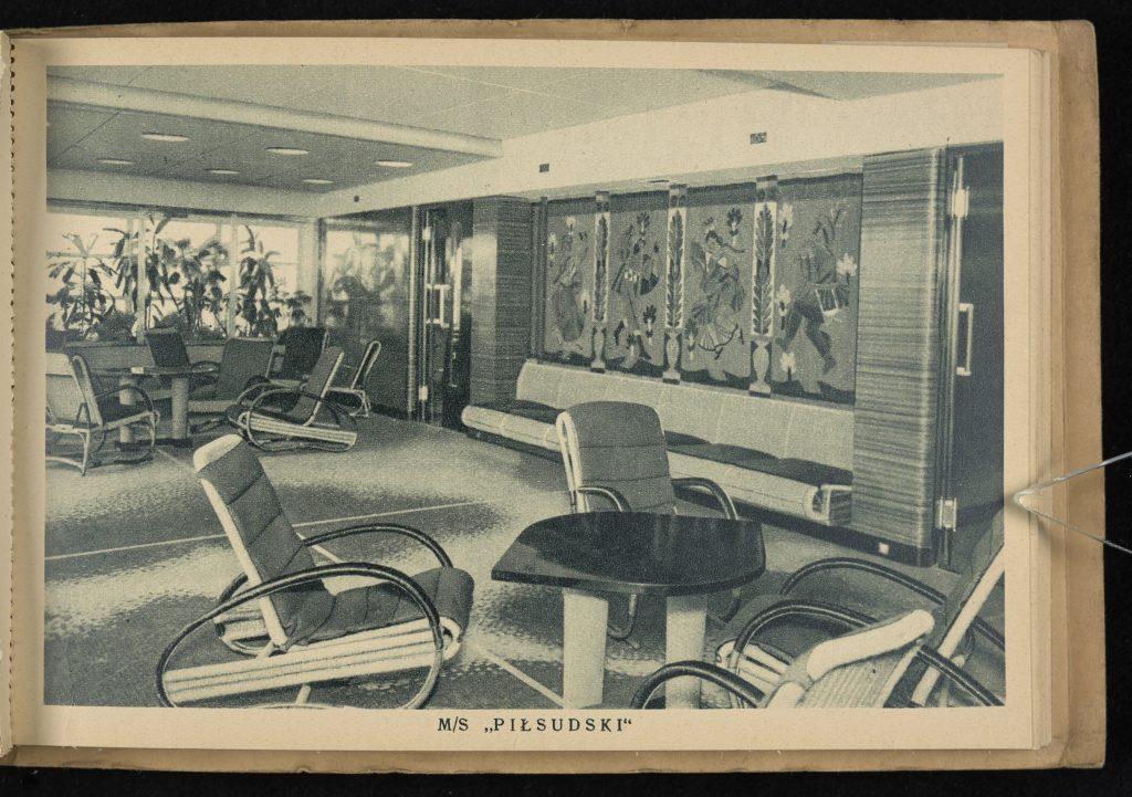 na pierwszym planie stolik z krzesłami, na ścianach werandy obrazy, w tle rośliny doniczkowe