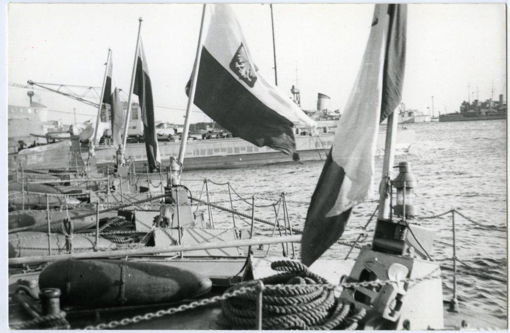 cztery polskie bandery na zacumowanych obok siebie w porcie okrętach