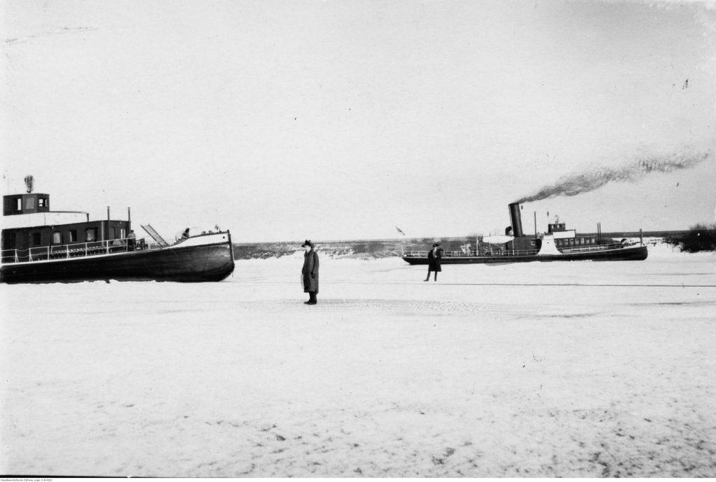 dwa pracujące statki na zamarzniętej rzece