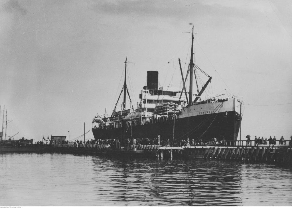 """""""Kentucky"""" przewożący emigrantów podczas postoju przy drewnianym molo pasażerskim."""