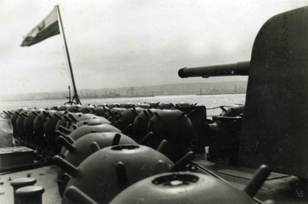 miny ułożone w dwa rzędy, na drugim planie bandera okrętu