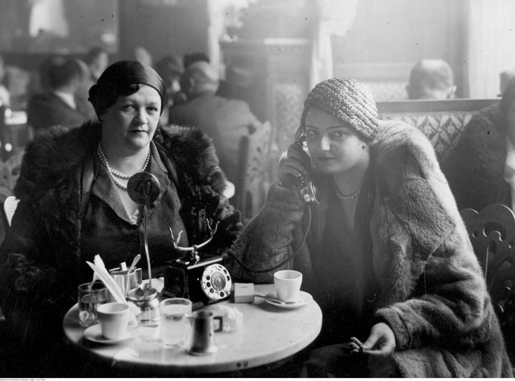 Goście restauracji siedzący przy stolikach. Na pierwszym planie widoczne dwie kobiety, jedna z nich rozmawia przez telefon stojący na stoliku.