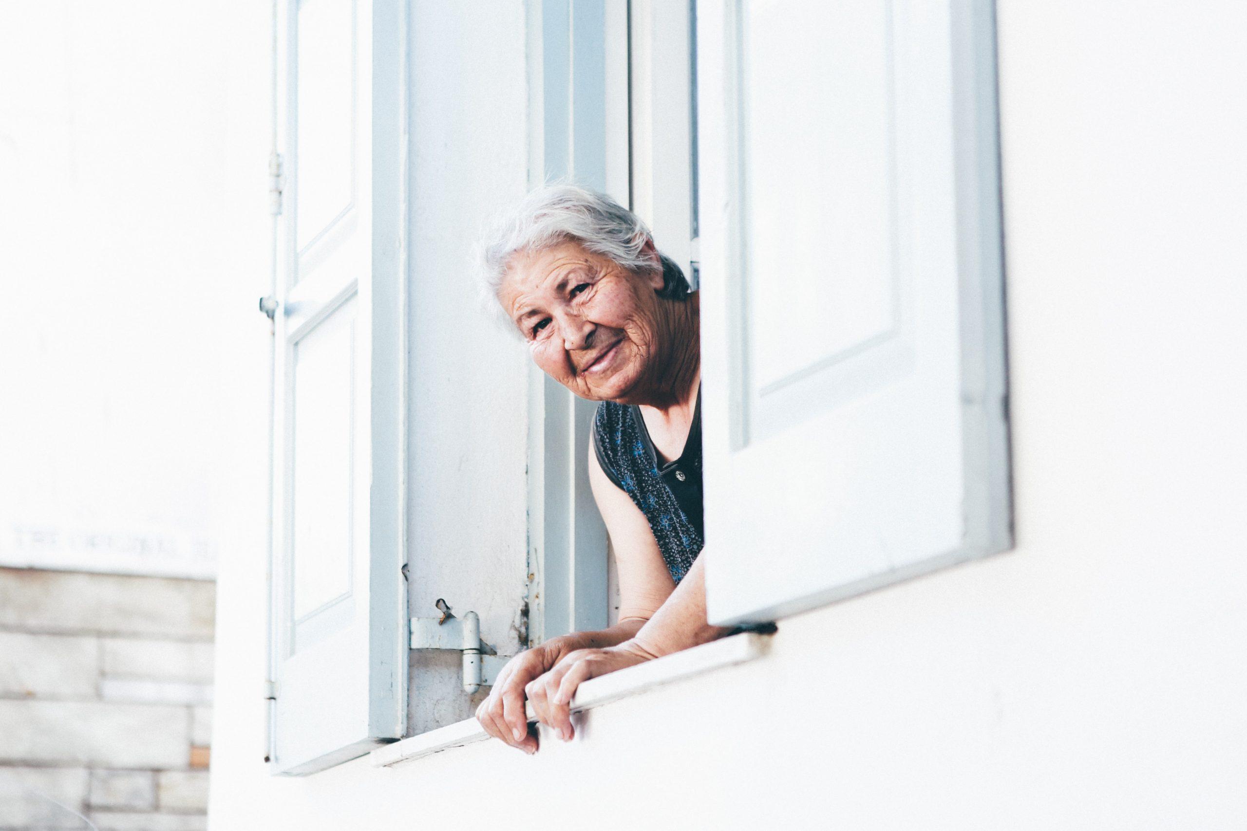 starsza pani wyglądająca przez okno