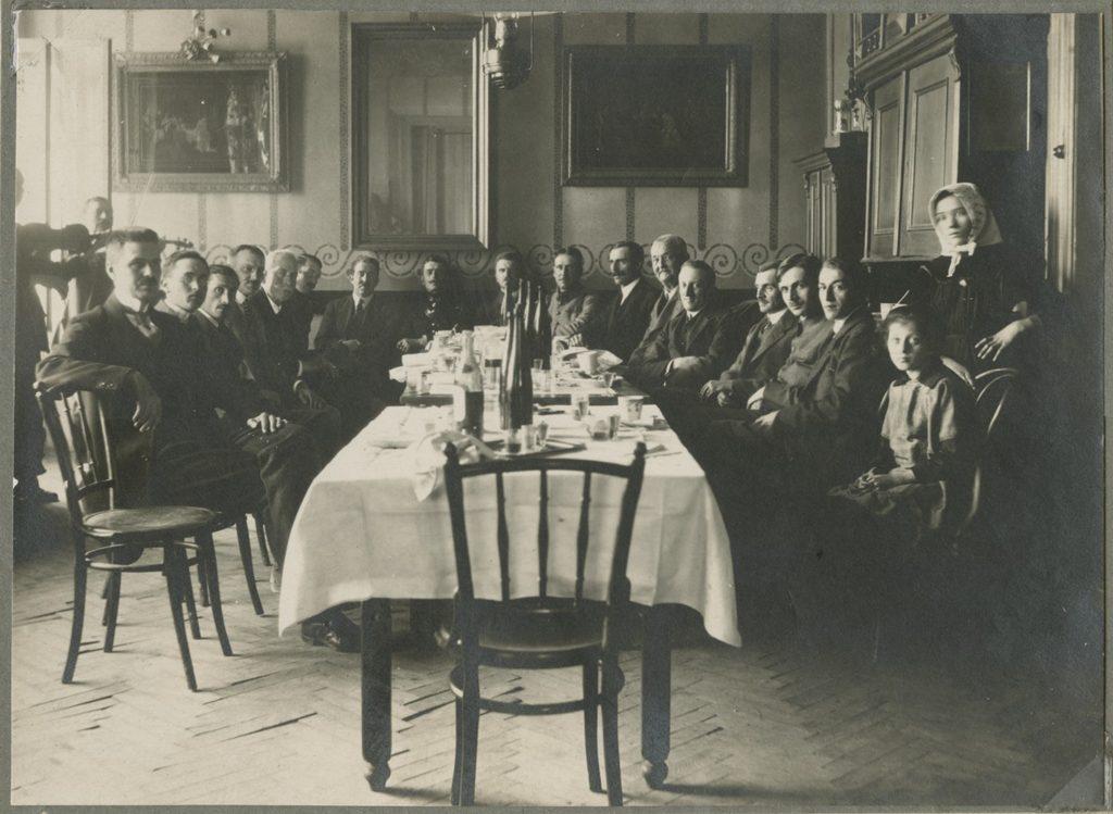 grupa ludzi siedząca wokół ozdobnie zastawionego stołu