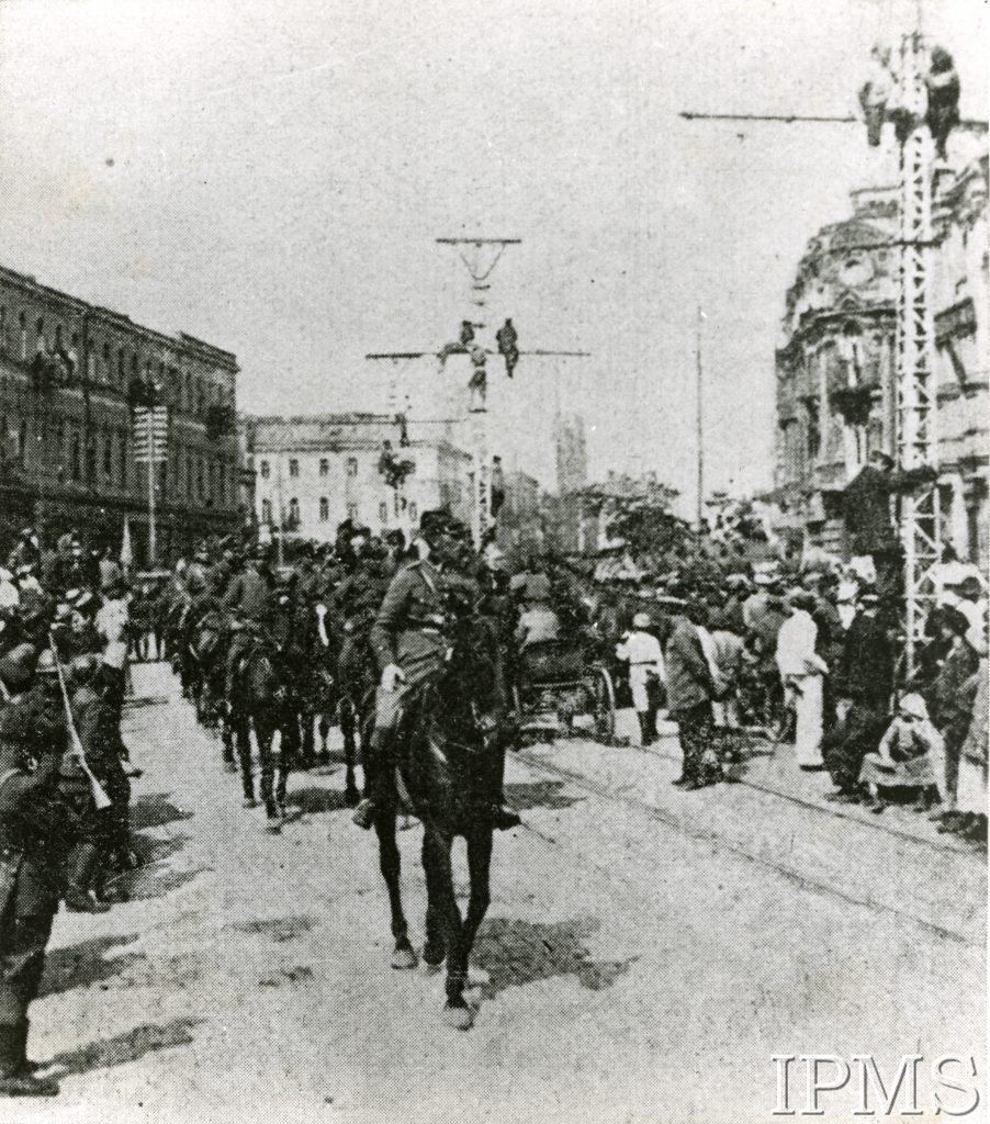 żołnierz na koniu na ulicy Kijowa, za nim oddział, po bokach gapie