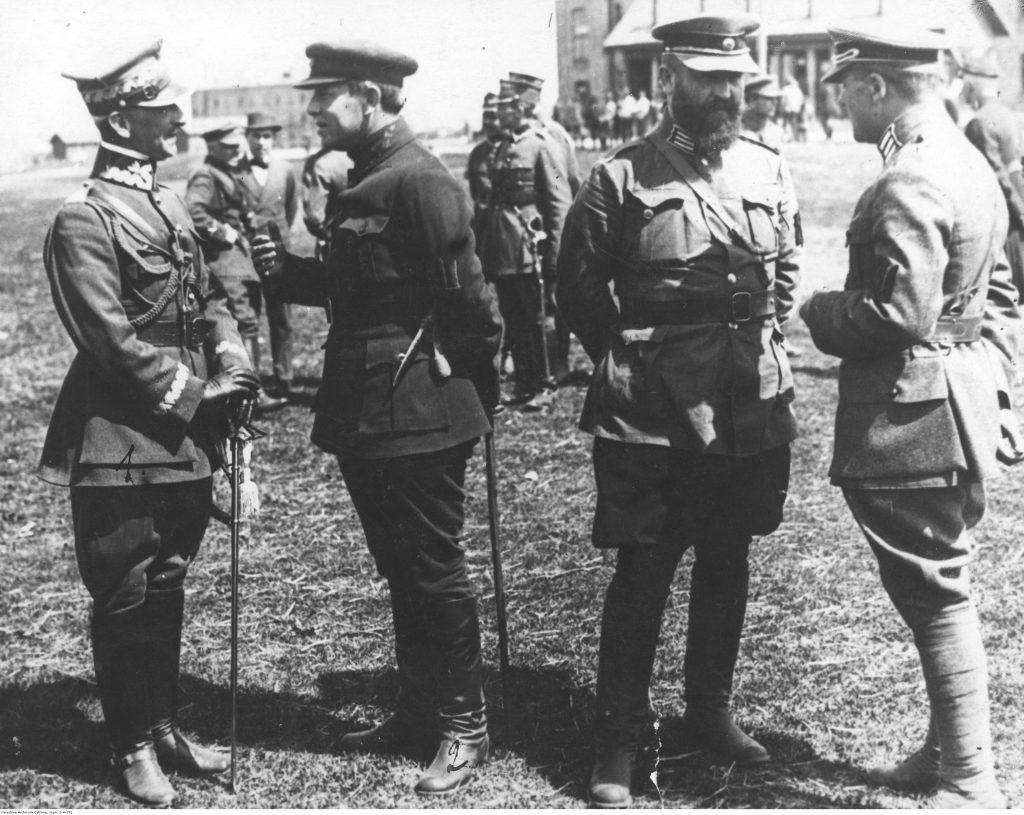 na pierwszym planie czterech żołnierzy rozmawiających w parach, w tle inni