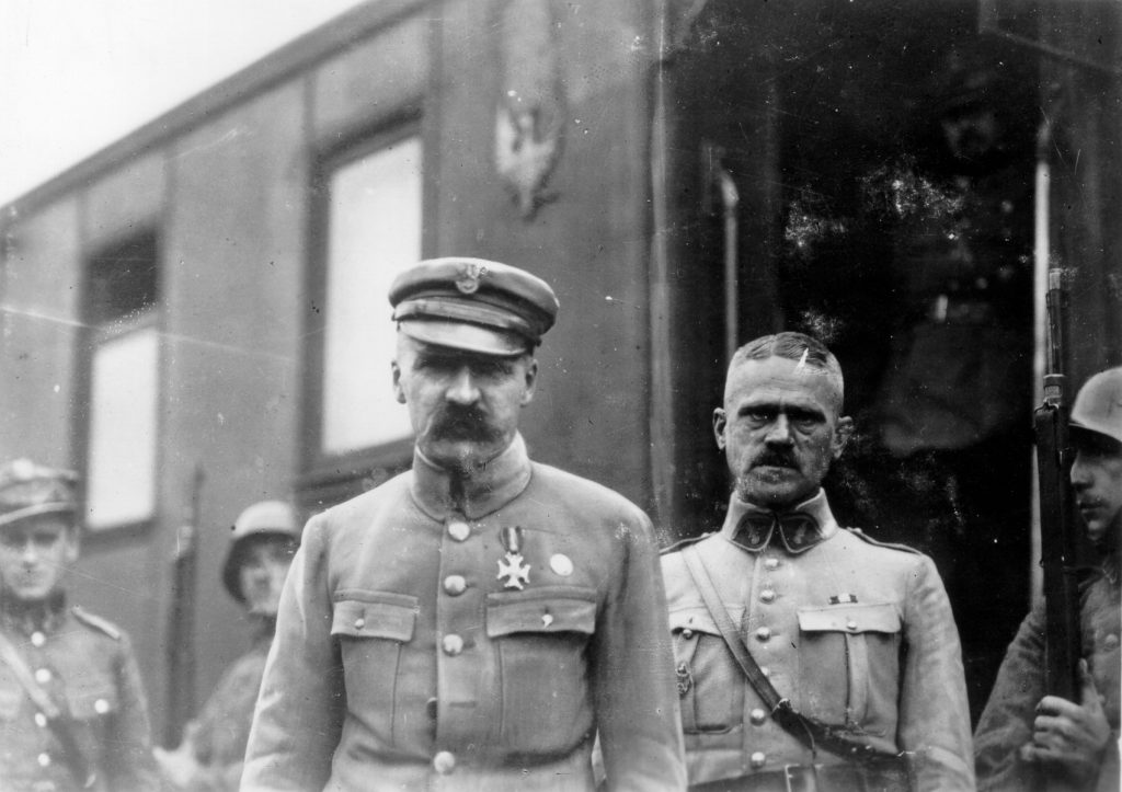 dwóch mężczyzn przed pociągiem, w tle trzech żołnierzy