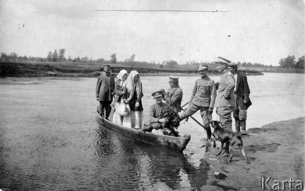 kobiety i żołnierze w łódce przybijają do brzegu rzeki gdzie czekają 3 mężczyźni