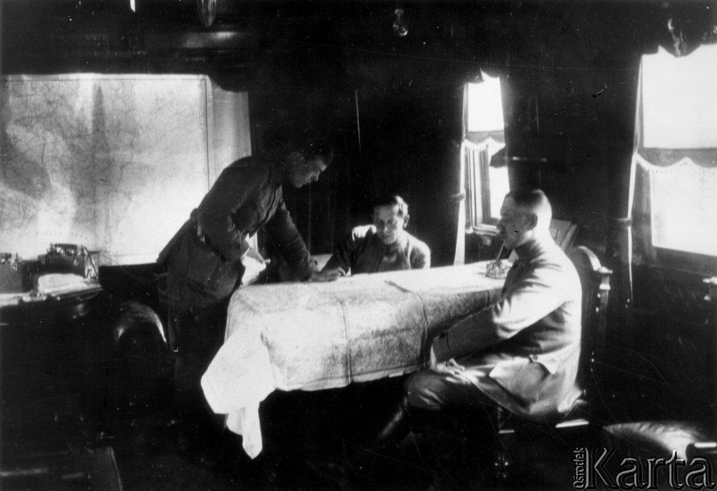 trzech mężczyzn przy stole w wagonie kolejowym