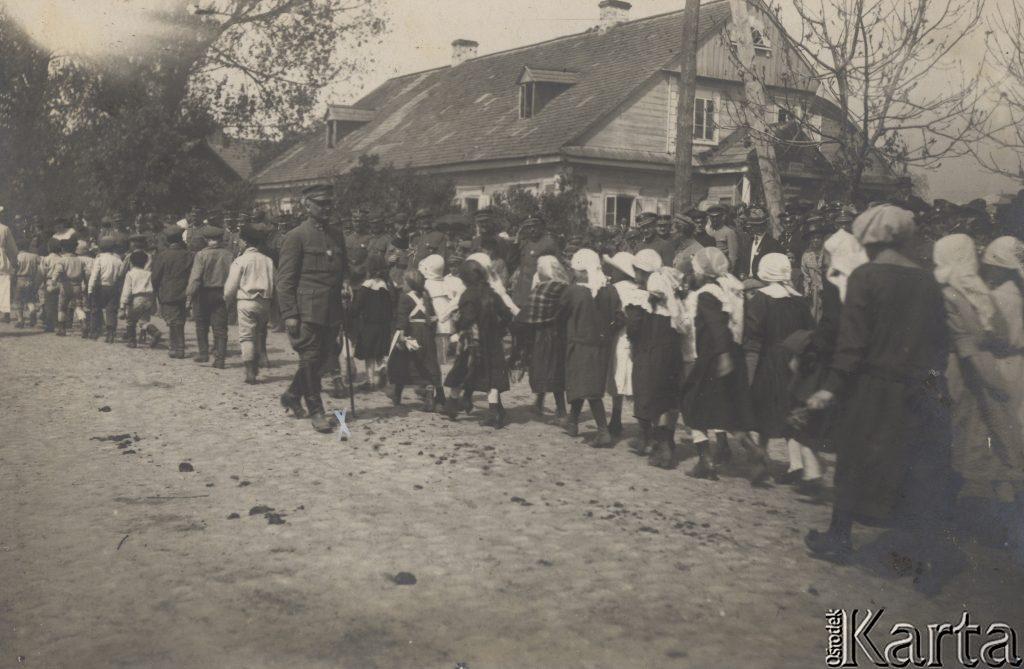 pochód ładnie ubranych dzieci na ulicy, w tle budynek