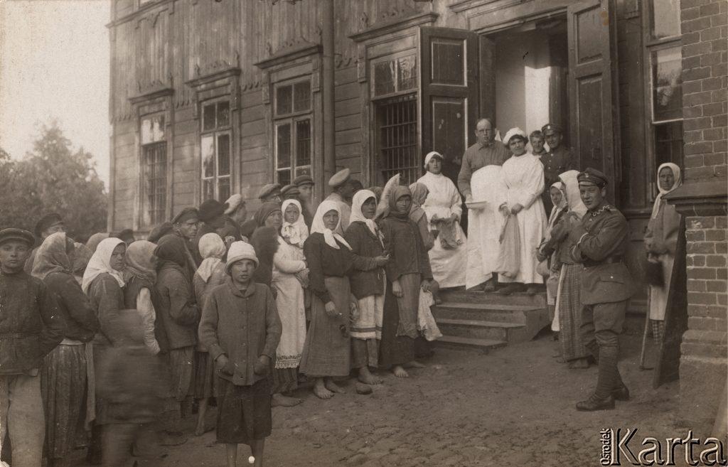 kolejka ludzi u wejścia do budynku
