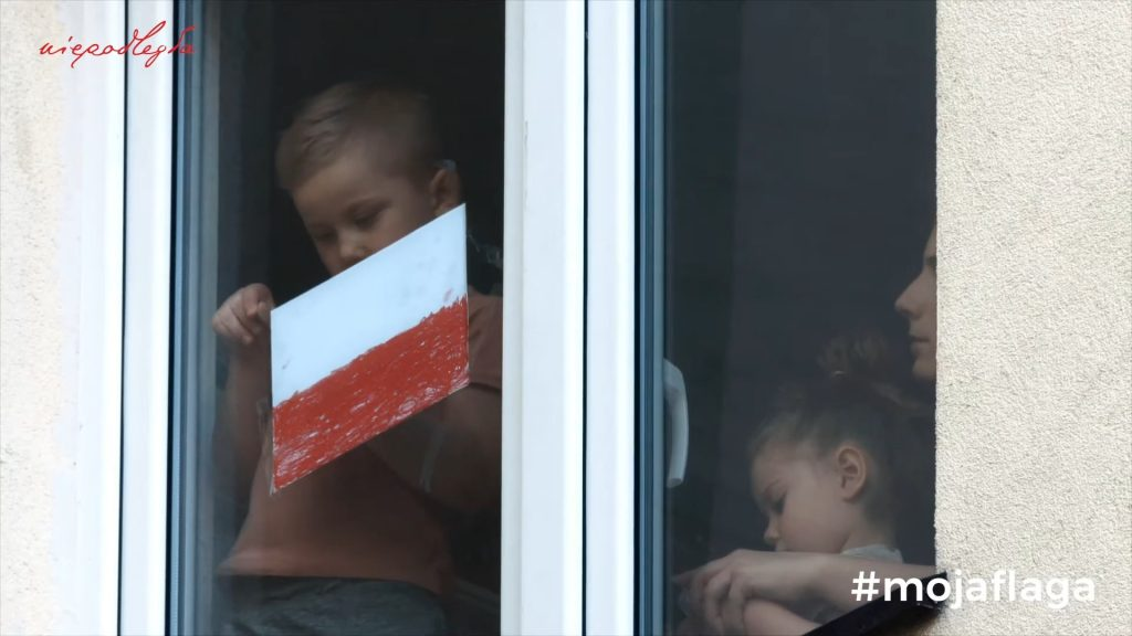 chłopczyk w mieszkaniu przykleja ręcznie wykonaną flagę polski do okna, obok asystują mu mama i siostra