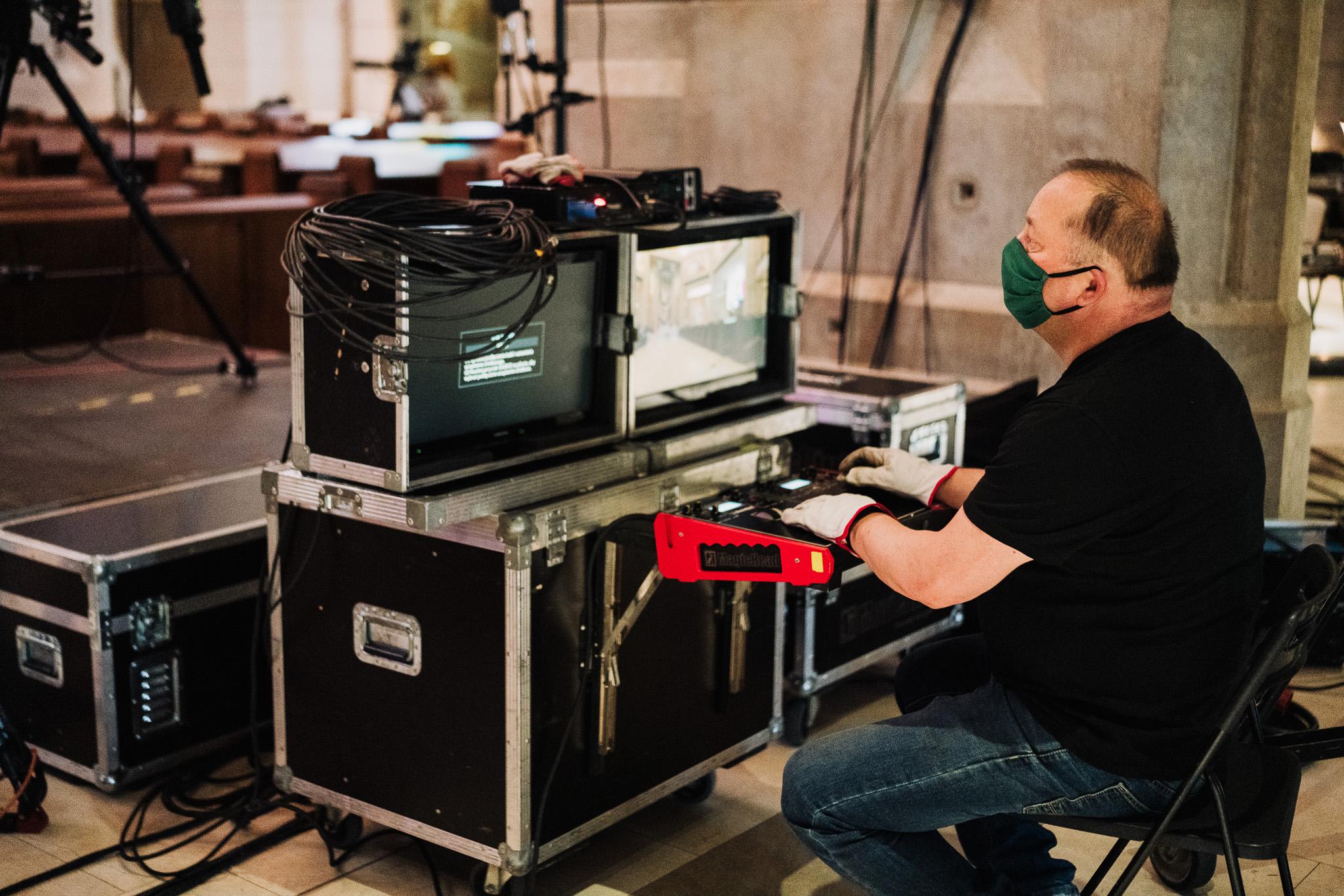 operator kamery przed swoim pulpitem w rękawiczkach i z maseczką na twarzy