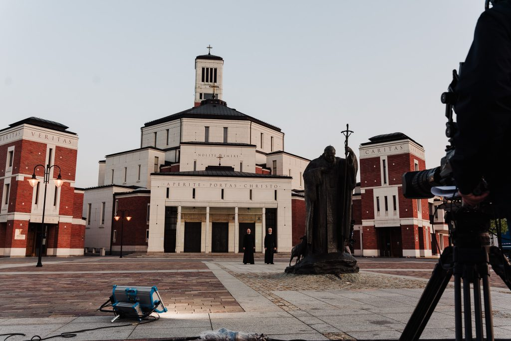 budynek sanktuarium JP II, na pierwszym planie kamera, dalej w centrum pomnik JPII, a dalej II mnisi przed budynkiem