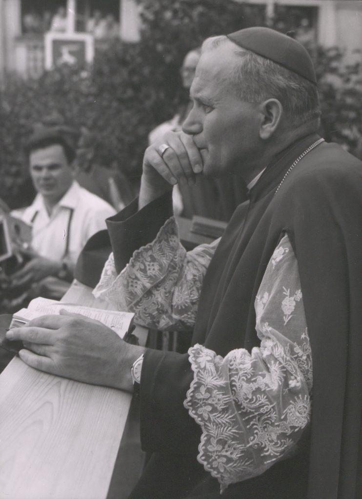 zamyślony biskup nad książką w tle inne postaci