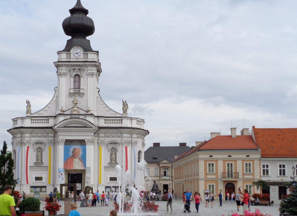 rynek wadowic, basylika udekorowana portretem jana pawła i flagami papieskini