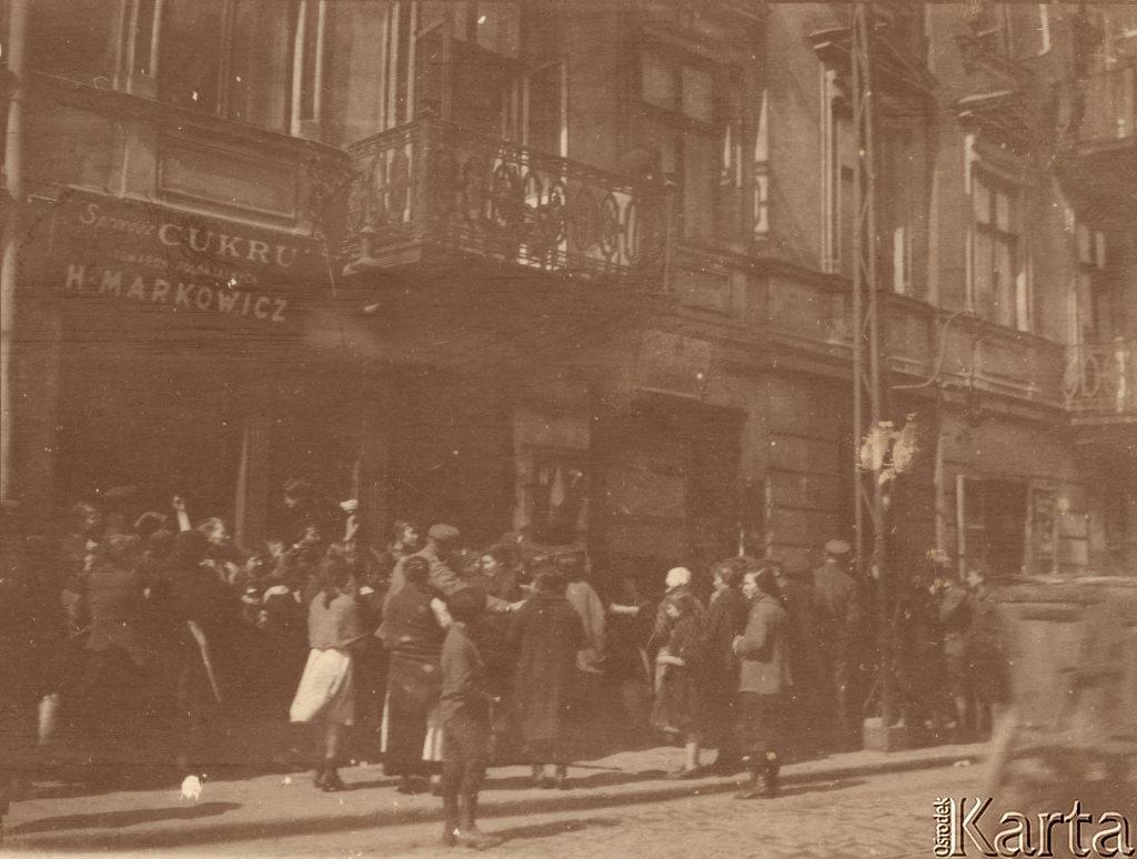 tłum ludzi czekających na ulicy na wejście do piekarni w przyziemiu kamienicy