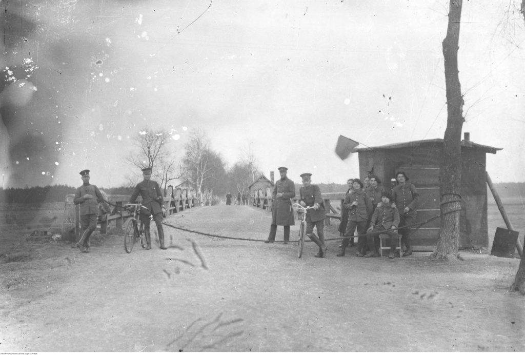 droga przedzielona sznurem, z boku drewniany posterunek graniczny, ustawieni żołnierze