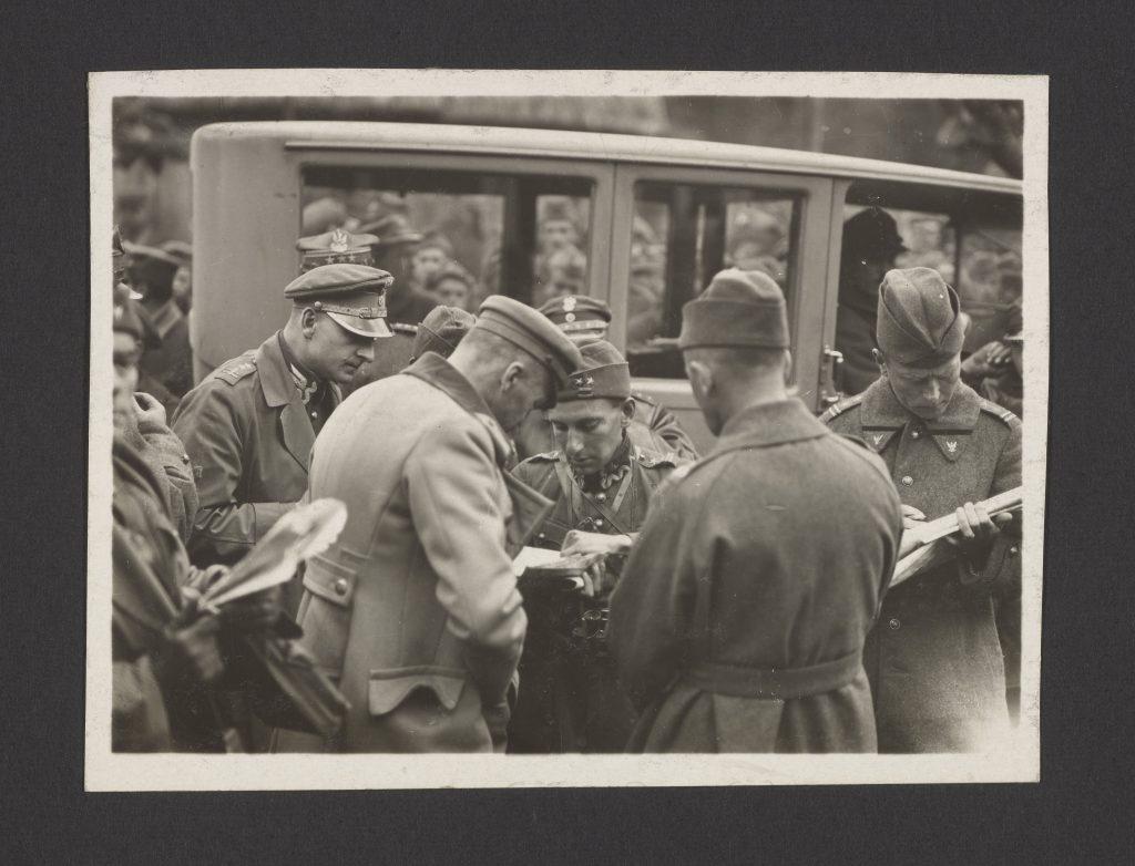 Józef Piłsudski przyjmujący meldunki na froncie, tłum żołnierzy i w tle auto